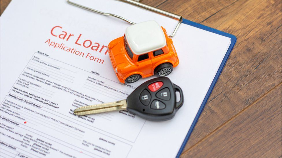 Car key laying on top of a car loan application