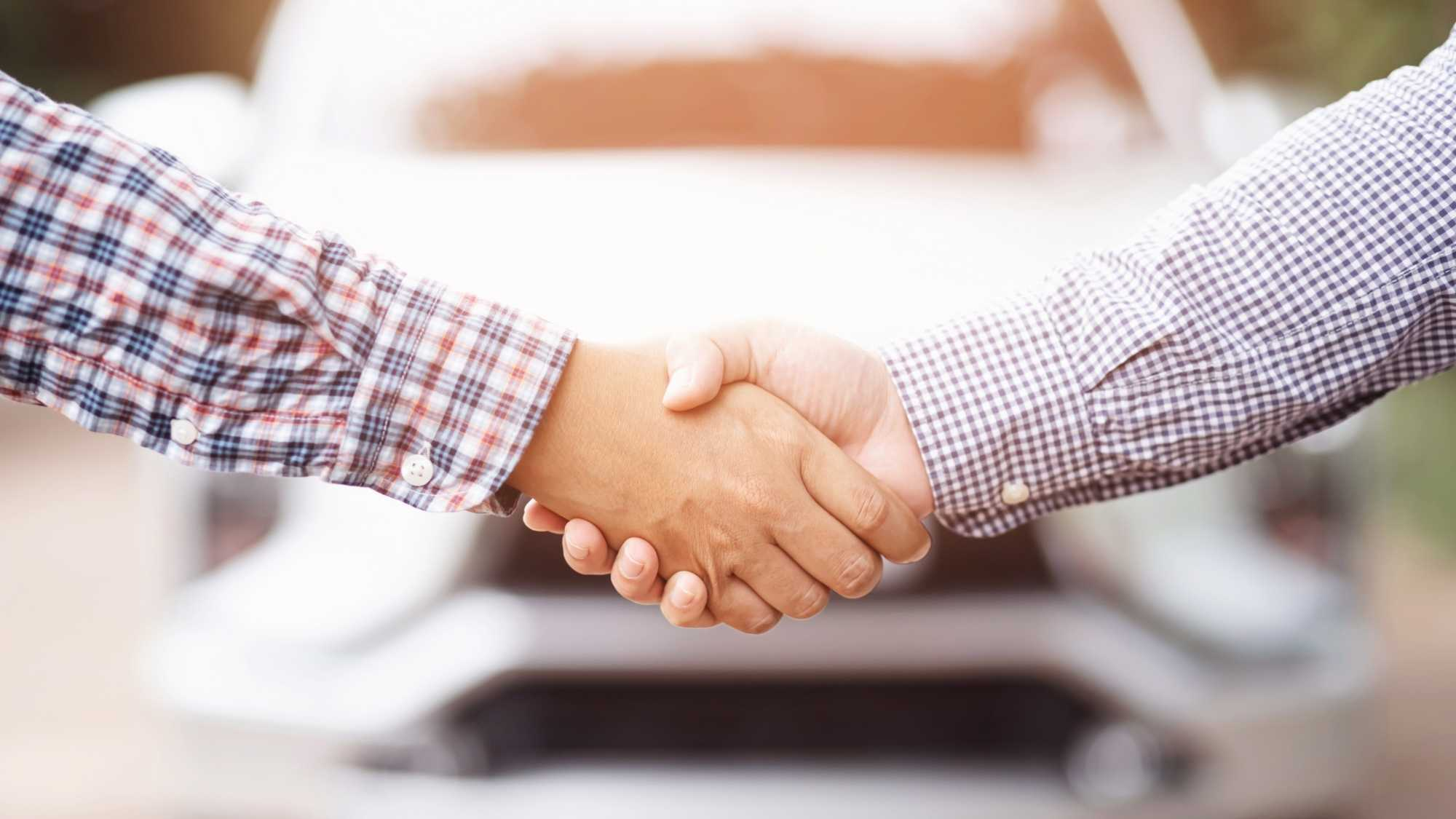 two guys shaking hands after selling a car privately